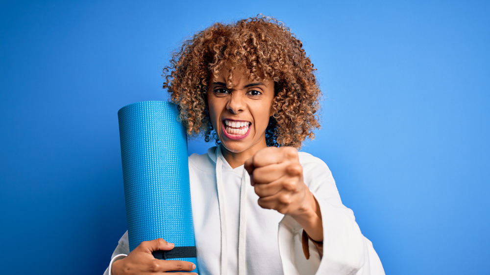 Woman holding up a fist and a yoga mat