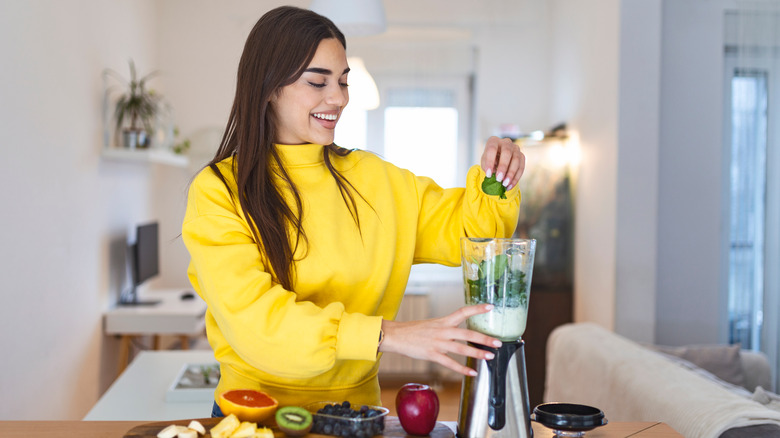A woman makes a smoothie at home