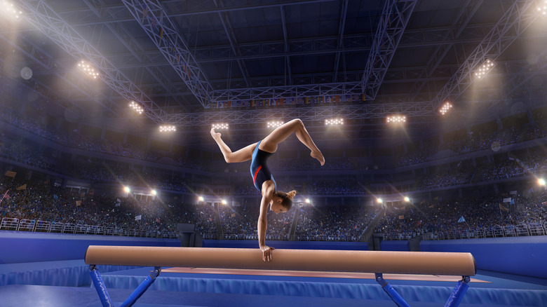 A female gymnast competes on the balance beam