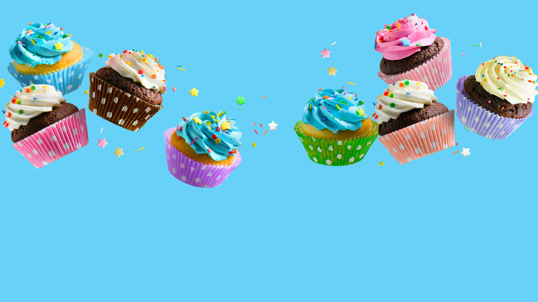 Eight cupcakes up in the air surrounded by sprinkles