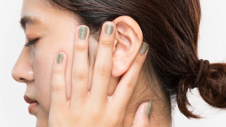 Woman massaging her ear