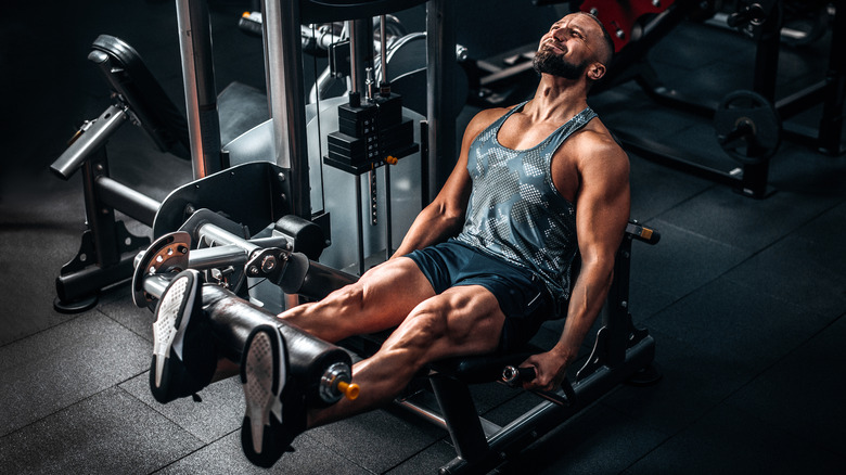 muscular man on leg machine in gym