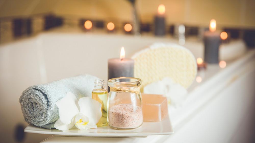 A bathtub with candles, soap, salts, etc.