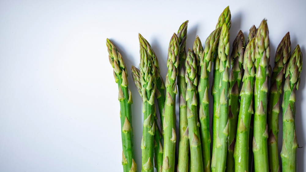 Stems of asparagus laid out on a neutral background