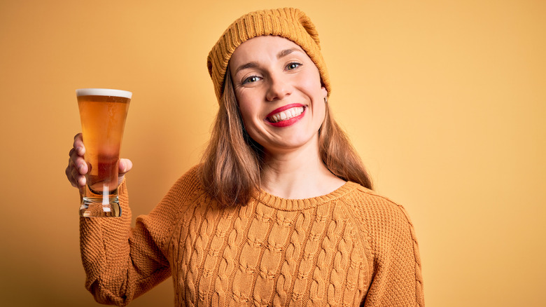 smiling young woman clad in all yellow holding a beer