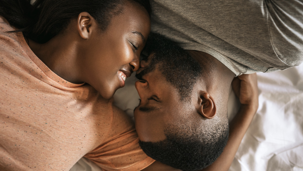 Close up of a couple's faces as they lay in bed