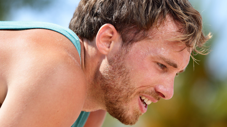 Male runner bending over with exhausted facial expression