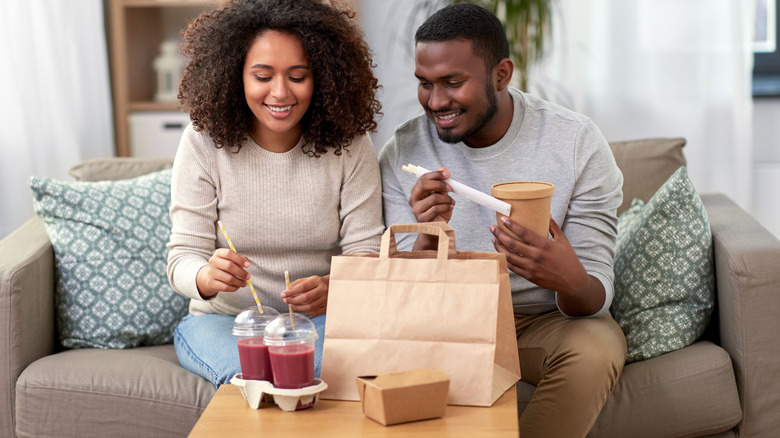 Young couple on the couch eating take-out smoothies