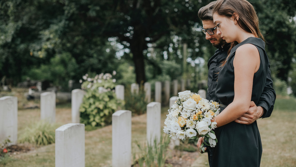 couple standing at gravesite