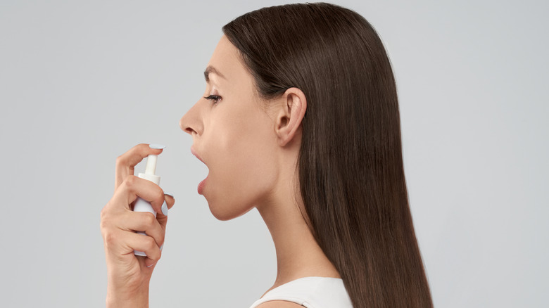 Woman holding mouth spray