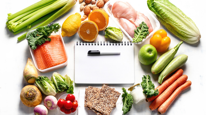 Healthy food scattered around a notepad