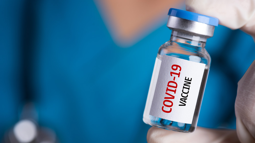 """Gloved hand holding vial with """"COVID-19 vaccine"""" written on it"""