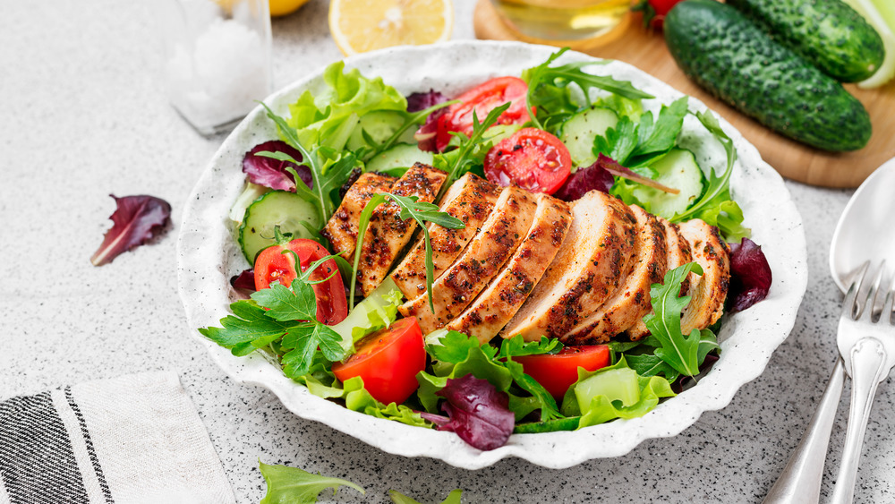 Salad in a bowl with grilled chicken on top