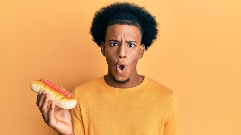 surprised man holding hot dog