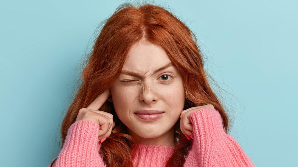 woman closing one eye, plugging ears