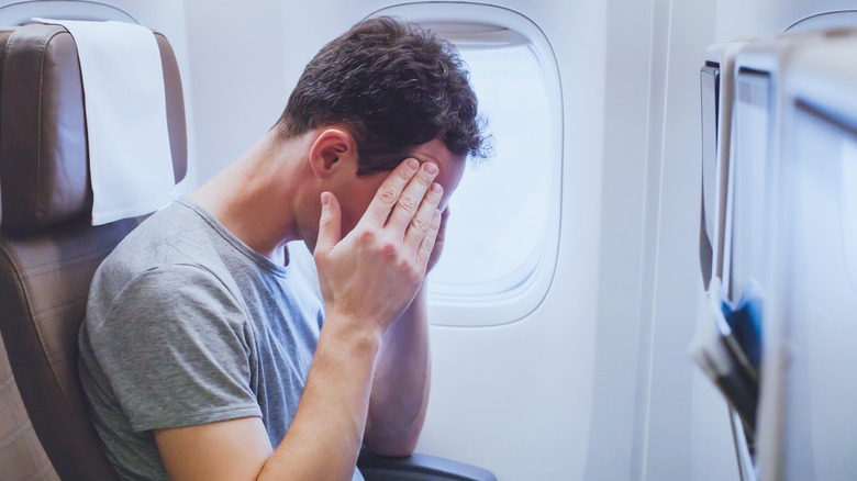 Man on airplane holding his head not feeling well