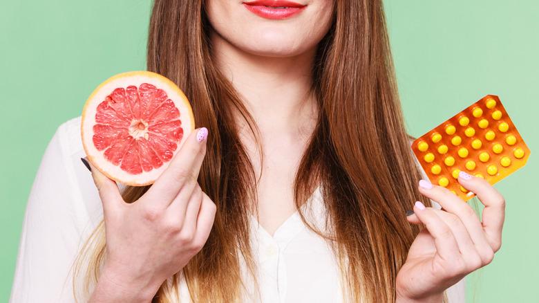 Woman holding grapefruit and pills