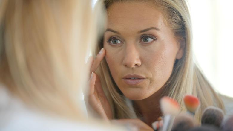 Woman analyzing skin in mirror