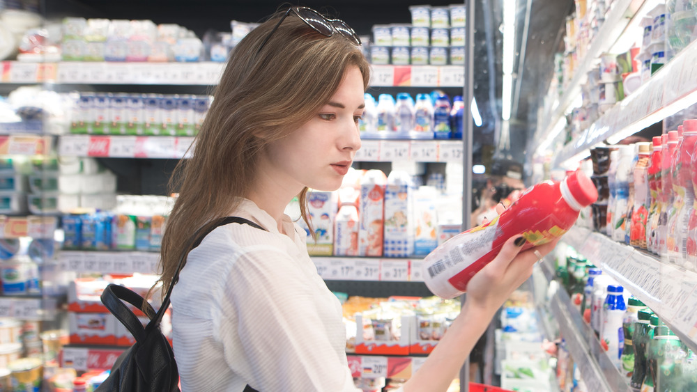 woman reading nutrition label in grocery store