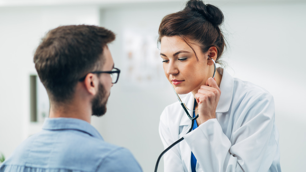 doctor listening to patient's heart with stethoscope