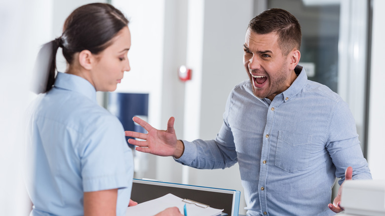 A man in a light blue shirt yelling at a nurse with a clipboard in a doctor's office