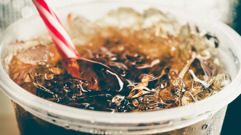Bubbly dark soda with ice cubes and straw