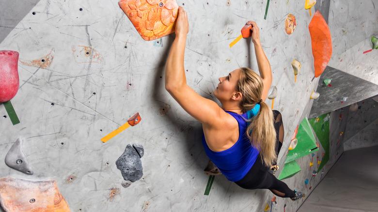 A woman climbing an indoor rock wall