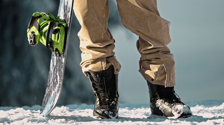 Close up of person's legs standing in the snow next to a snowboard