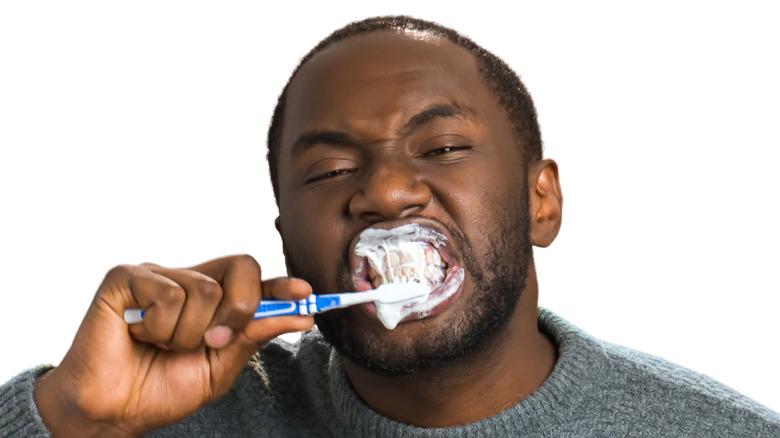 man brushing teeth hard