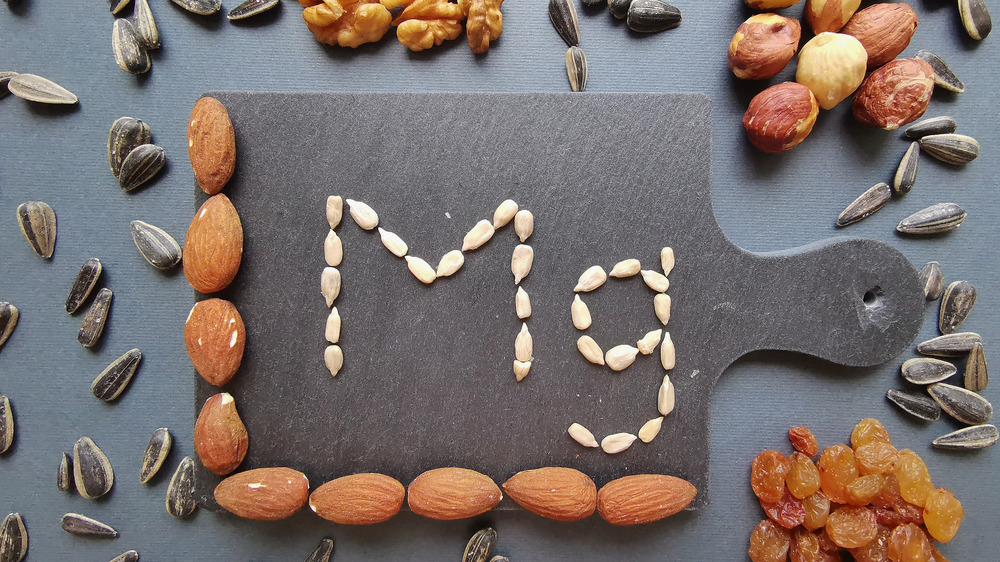 """Nuts and seeds surrounding letters """"Mg"""" spelled out in sunflower seeds"""