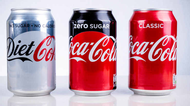 A can of zero sugar Coke between a can of diet Coke and a can of classic Coke
