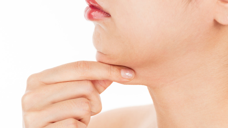 Woman pinching the fat on her chin