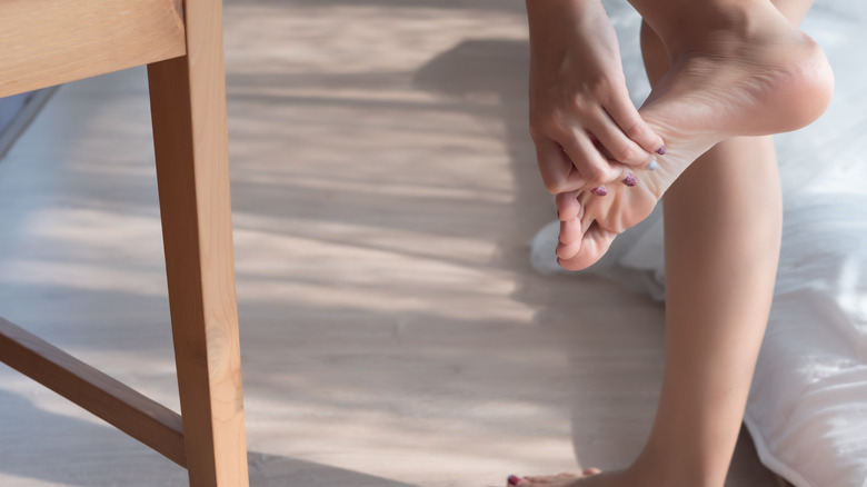 Close up of woman grabbing her toe in pain