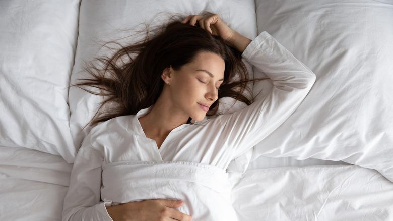 A woman sleeps peacefully on her back