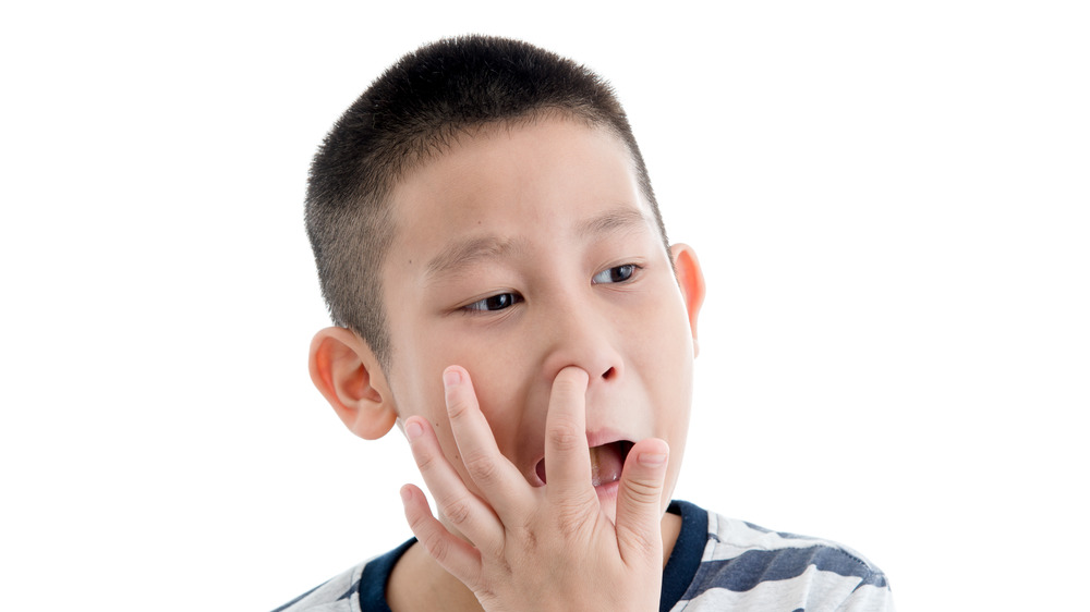 Young boy picking his nose with all white background