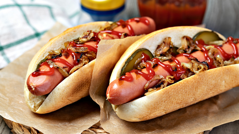 Two hot dogs with various toppings