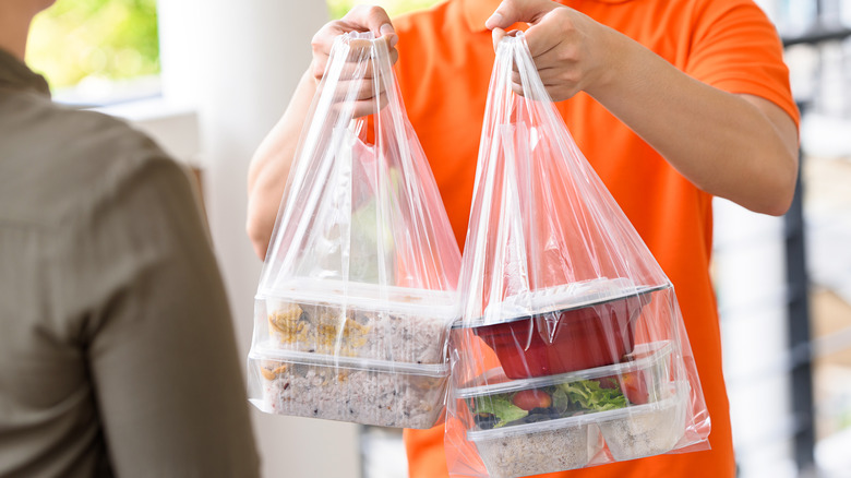 Person handing another person food containers wrapped in plastic bags