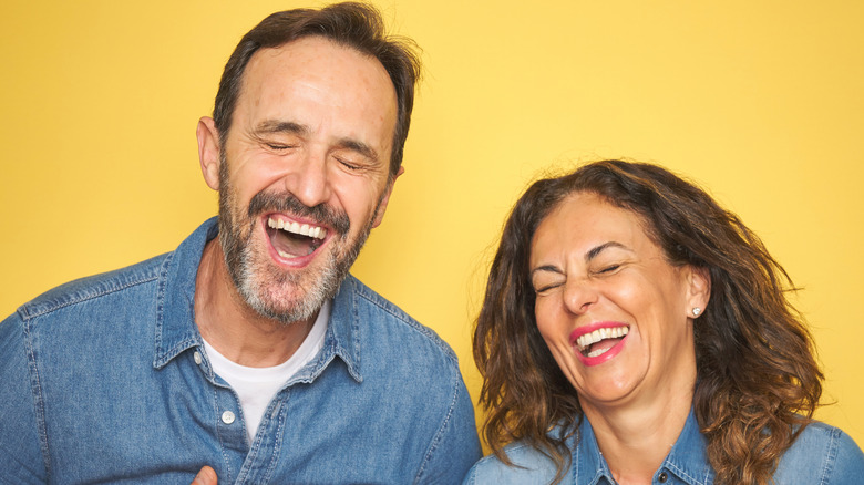 Couple laughing on yellow background