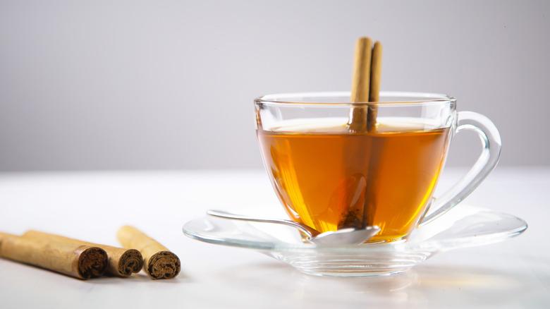 A glass of cinnamon tea with cinnamon sticks next to it