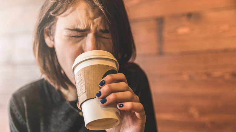Woman drinking a cup of coffee that is too hot