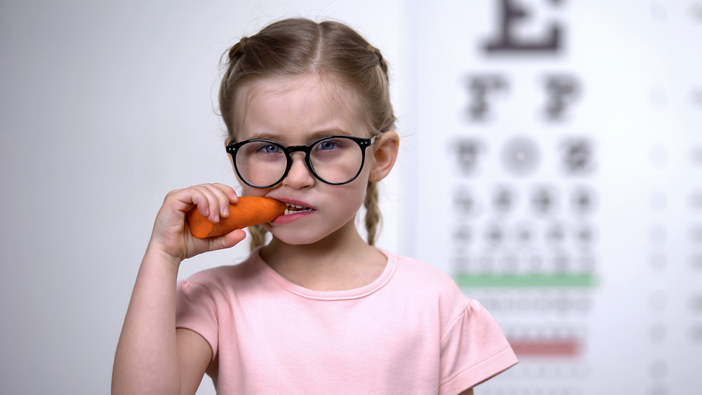 young child wearing glasses, chewing on a carrot, with a vision test in the background