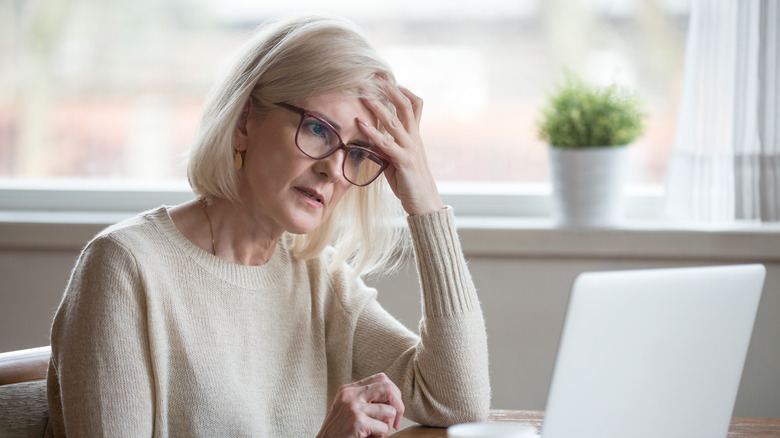 older woman sitting at her computer looking forgetful
