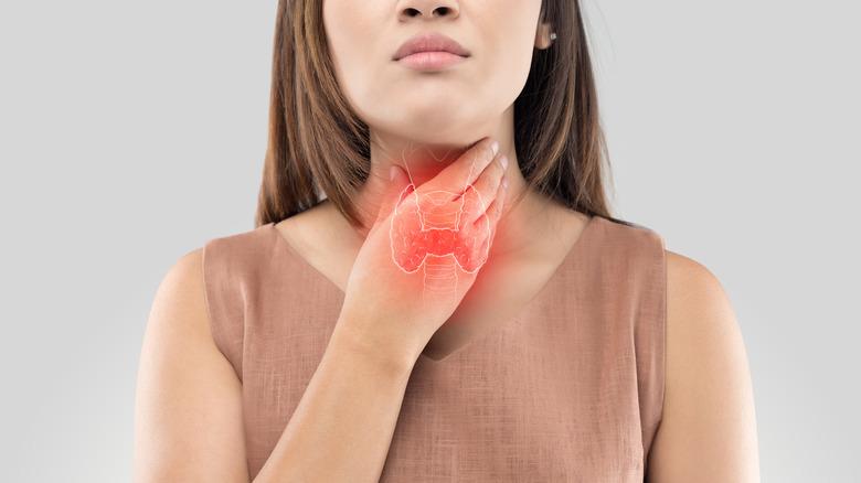 Woman touching her sore throat