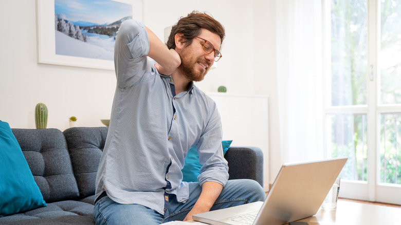 Man wearing glasses, sitting on couch holding his neck, laptop on coffee table
