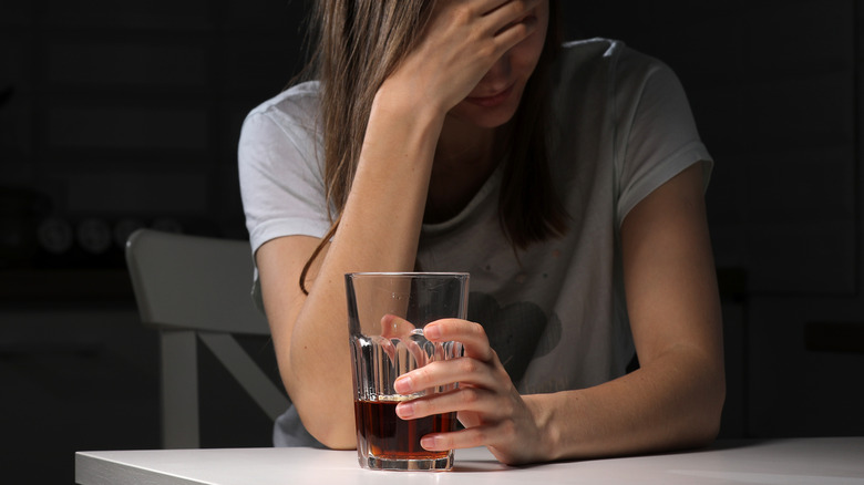 woman holding drink and looking sad