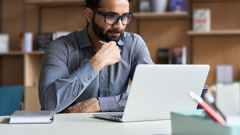 Man with glasses using laptop