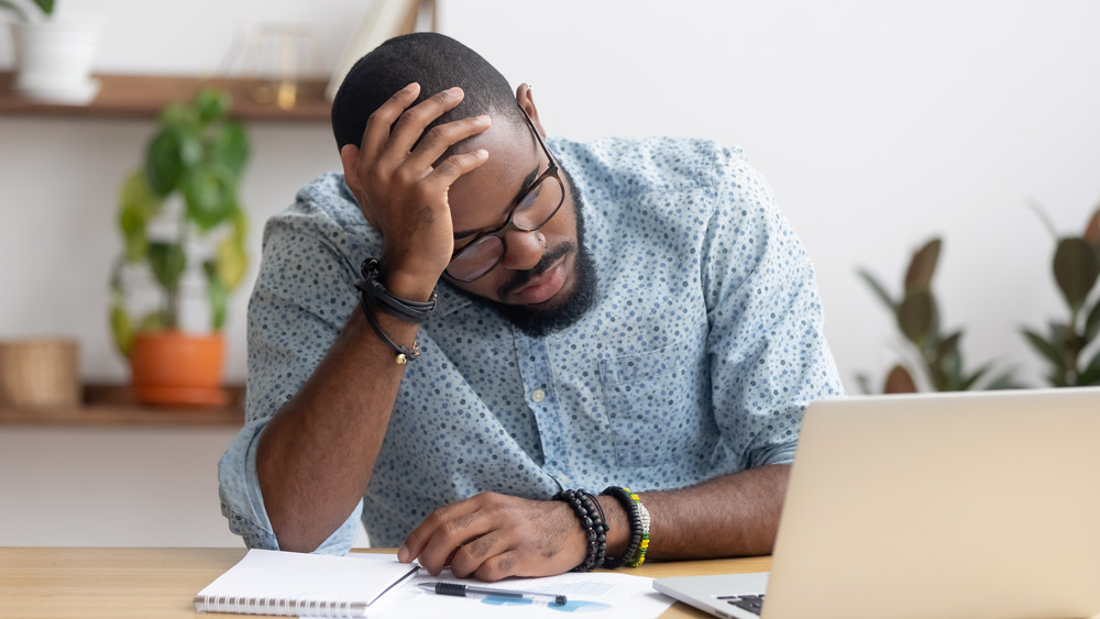 Man tired at work with laptop