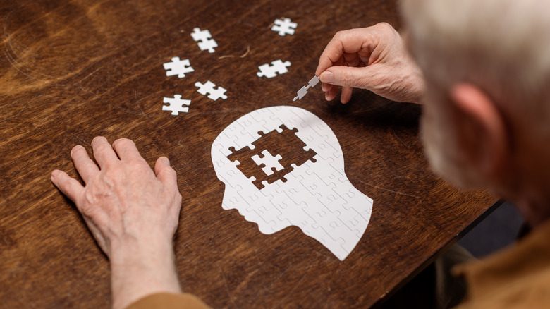 Person doing a paper puzzle in the shape of a human head