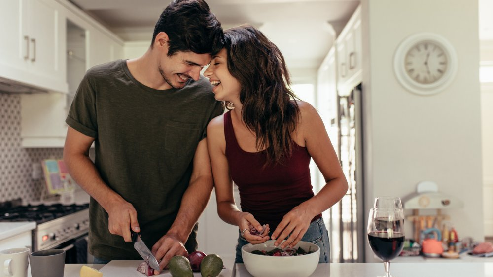 man and woman preparing food in the kitchen
