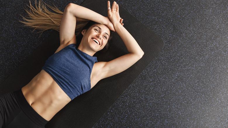 Woman lying on mat smiling